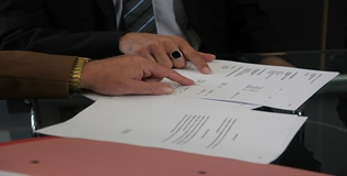 Image of two people's hands pointing at a document on a table.